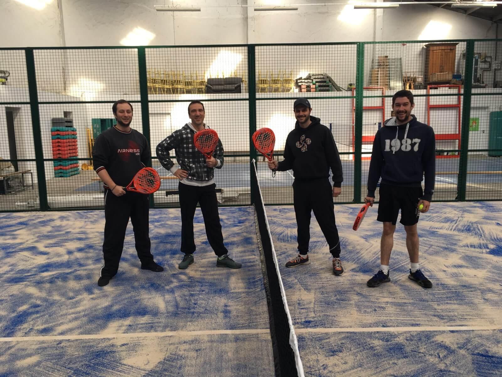 4 amis sur un terrain de Padel Tennis indoor avec raquette à la main